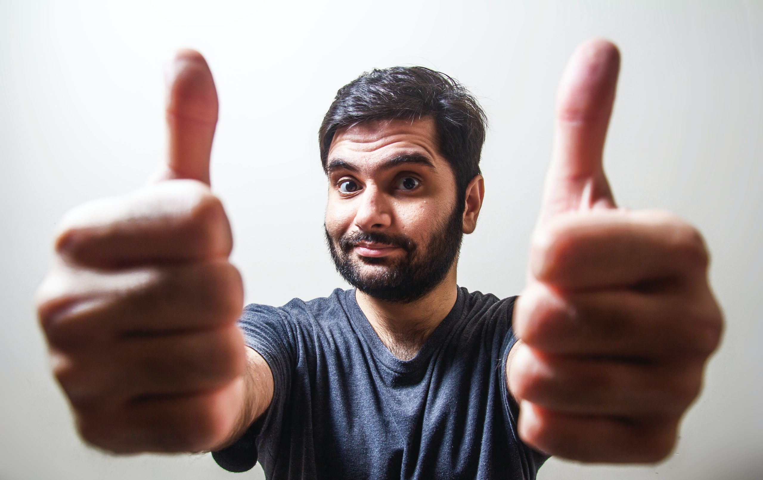A man makes a thumbs up sign with both hands.